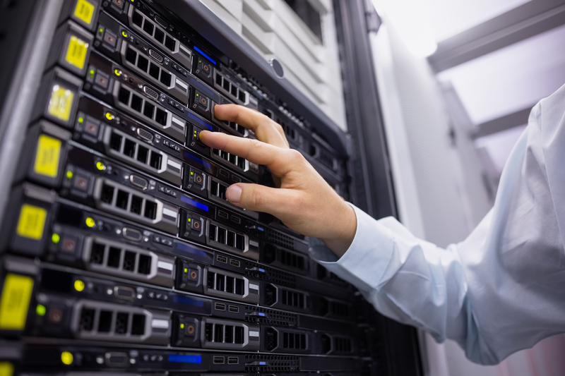 Technicican working on server tower in large data center